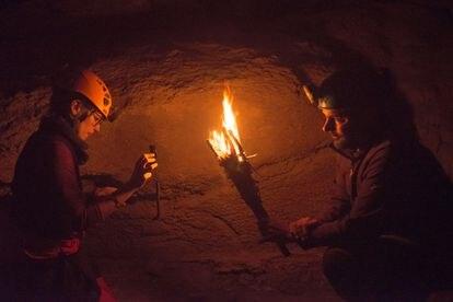 Mª Ángeles Medina y Diego Garate, midiendo la luz de una antorcha en la cueva.