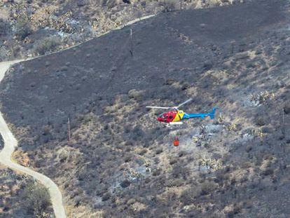Vista desde la Cruz de Tejeda en la mañana de este lunes de un helicóptero en la zona arrasada por el incendio de Gran Canaria.