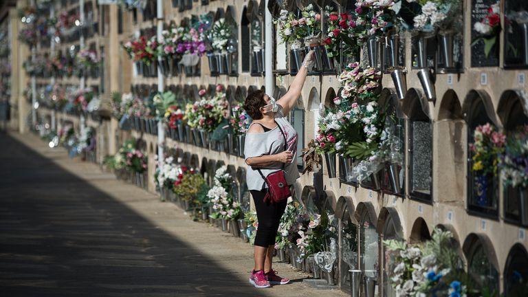 Una mujer deposita flores, en un cementerio de Barcelona, este lunes.