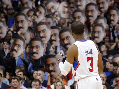 Chris Paul celebra una canasta con los seguidores de los Clippers, que llevan caretas con su cara.