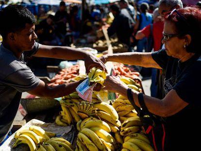 Una mujer compra fruta en un mercado de Caracas este miércoles.