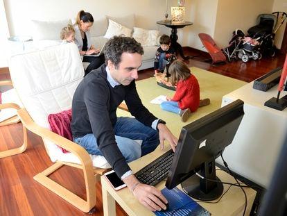 Una pareja teletrabaja mientras cuida de sus tres hijos.