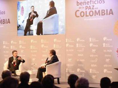 El presidente de Colombia, Juan Manuel Santos, conversa con el presidente del Grupo PRISA, Juan Luis Cebrián, durante el foro celebrado en Bogotá.