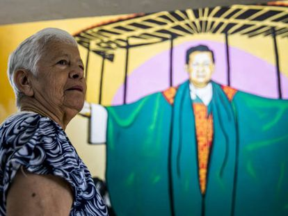 La religiosa Maritze Trigos frente a un mural con la imagen del párroco Tiberio Fernández, en el parque monumento en homenaje a las víctimas de la masacre de Trujillo.