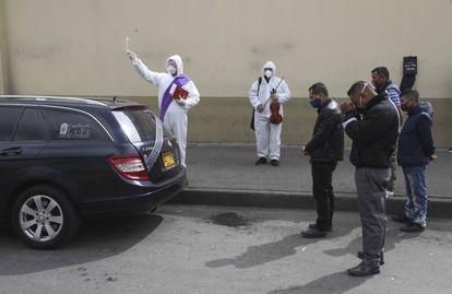 Un clérigo rocía agua bendita mientras familiares se reúnen alrededor del coche fúnebre que transporta a una víctima del COVID-19 al cementerio Chapinero en Bogotá, Colombia, el pasado 6 de agosto de 2020.