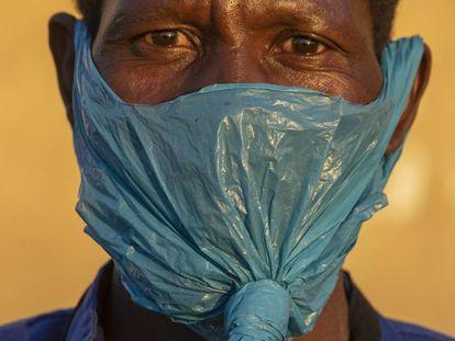 Un hombre usa una bolsa de plástico en la cara como mascarilla facial contra la propagación del coronavirus, en Johannesburgo, Sudáfrica.