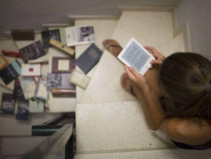 Una joven lee un libro electrónico junto a varios libros en papel.