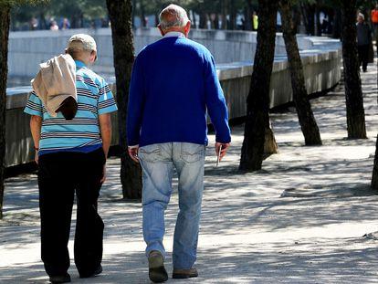 Dos personas de avanzada edad pasean por un parque de Madrid.