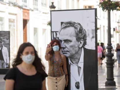 Una mujer posa junto a un cartel de José Coronado en la exposición 'Cine de cerca' en la calle Marqués de Larios, en Málaga.