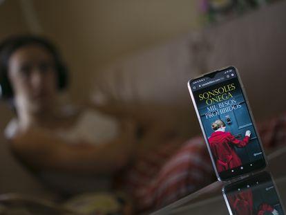 Una mujer escucha un audiolibro desde su teléfono móvil.