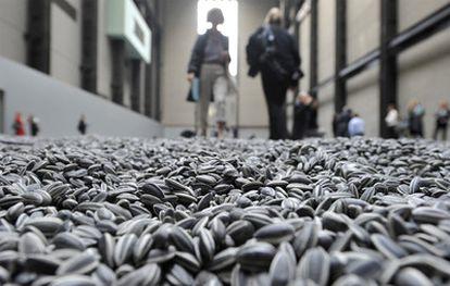 Visitantes de la Tate Modern caminan sobre las pipas de porcelana que componen la instalación <i>Sunflower seeds</i> .