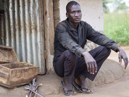 Alex Bongtiko, antiguo niño soldado del Ejército del LRA, delante de su casa con la caja de herramientas que usa para reparar las bicicletas y motos.