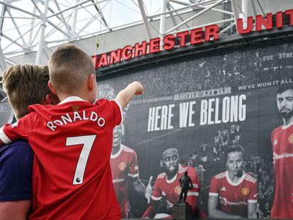 Un padre y su hjjo, con la camiseta de Cristiano frente a la fachada de Old Trafford.