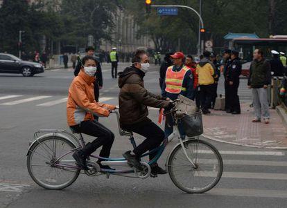 Una pareja china pasa ante el hotel de Pekín se reúnen los líderes.