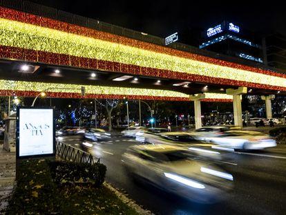 Luces de Navidad de Madrid con los colores de la bandera de España en el Puente Juan Bravo, en el primer día de encendido de las luces de Navidad.
