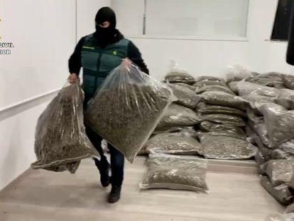 Un agente carga dos sacos de la marihuana incautada en Almería.