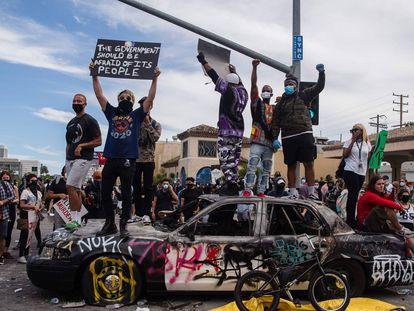 ManifestManifestantes saltan sobre un vehículo policial dañado en Los Ángeles.