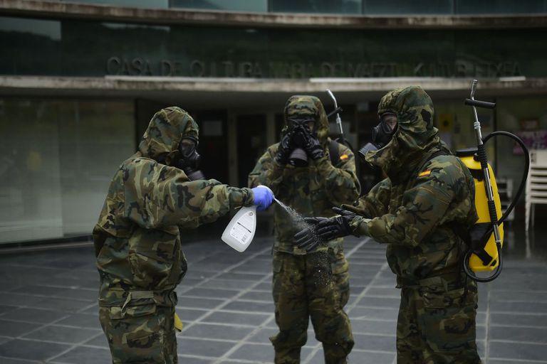 Militares del Regimiento América 66 de Pamplona se lavan los guantes después de desinfectar un establecimiento en la capital navarra el pasado 22 de abril.