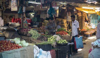 Un hombre con una bolsa de tela para hacer la compra adquiere legumbres en un mercado de Bombay.