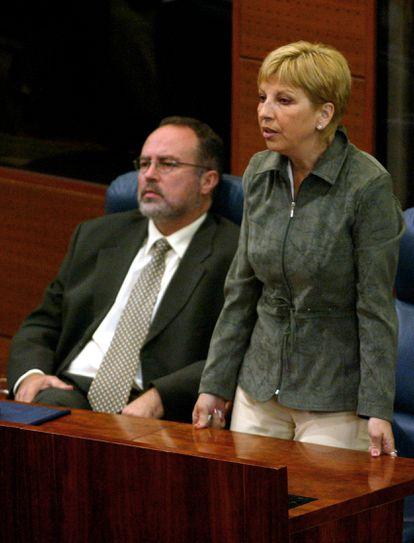 Teresa Sáez vota de pie, junto a Eduardo Tamayo, sentado, en sus escaños de la Asamblea de Madrid.