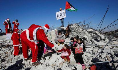 Un manifestate palestino vestido de Papá Noel entrega regalos a unos niños en los restos de una casa demolida por Israel en Belén.