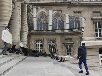 Dos trabajadores transportan un espejo en el que se refleja la Santa Capilla de París el pasado 5 de mayo.