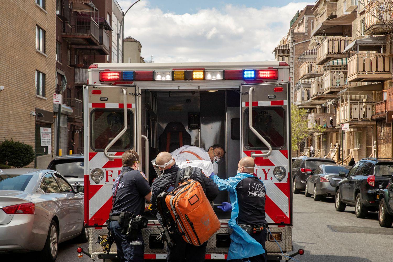 Profesionales sanitarios trasladan este jueves a un hombre en ambulancia en Nueva York.