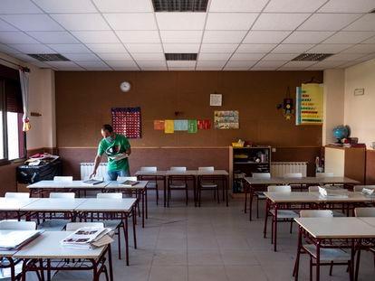 Un profesor prepara un aula para el inicio del curso en el colegio Fuente del Palomar de Alcorcón (Madrid).