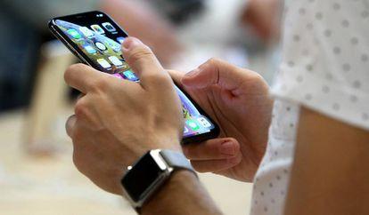 Un usuario sostiene un iphone en la tienda de Apple de la Puerta del Sol de Madrid.