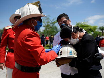 Bomberos de Guayaquil entregan a la hija de Luis Paez el casco de su padre, fallecido de covid-19, al igual que su madre, en esta ciudad ecuatoriana.