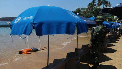Un soldado mira al hombre tiroteado en Acapulco.
