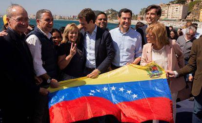 El presidente del PP, Pablo Casado, posa en Málaga, junto a representantes del PP andaluz, con una bandera venezolana.