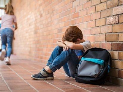 Un menor sentado en el suelo, tras ser víctima de un episodio de acoso escolar.