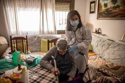 Una doctora atiende una anciana durante una visita domiciliaria en Les Roquetes del Garraf, Barcelona.