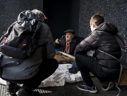 Dos educadores de la Fundación Arrels hablan con una persona que vive en la calle.