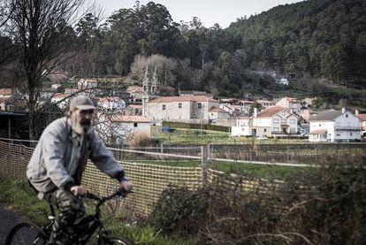 Un vecino de Outes pasa en bicicleta el pasado viernes cerca de la iglesia de Roo.