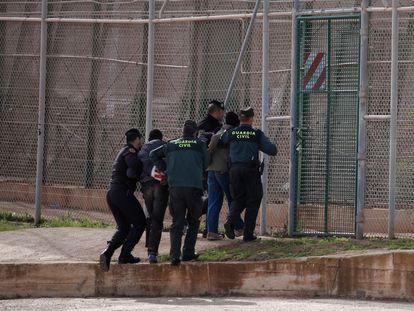 Unos agentes de la Guardia Civil expulsan a dos migrantes que acababan de saltar la valla de Melilla, en 2014.