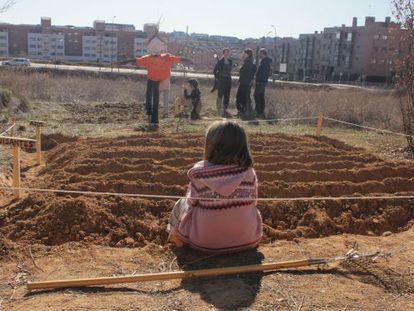 Una niña observa uno de los bancales del huerto de Montecarmelo.