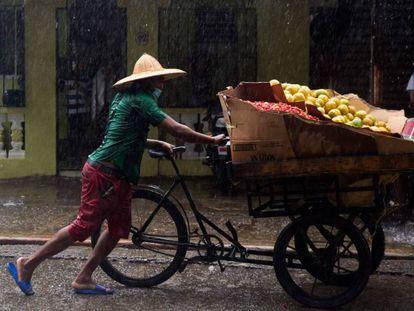 Un vendedor de mango con su puesto ambulante va a resguardarse ante las lluvias durante la tormenta Isaias, en Santo Domingo.