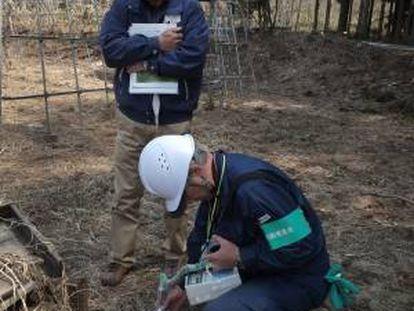 Yasushige Watanabe, un agricultor que se niega a regresar a su casa, en Miyakoji, observa cómo un técnico mide el nivel de radiación en un campo junto a su vivienda.