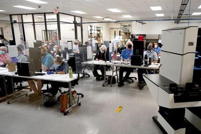 Trabajadores del centro electoral de Maricopa trabajan en el conteo de votos en la noche del miércoles.