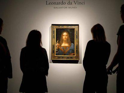 Empleados de Christie's, frente a la obra antes de ser subastada en 2017. En vídeo, el 'Salvator Mundi', el cuadro más caro de la historia, pone en jaque el rigor del Louvre.