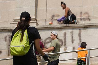 Kyle Rittenhouse, con gorra en el medio, limpiando pintadas en Kenosha, Wisconsin, el martes.