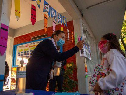 Una maestra toma la temperatura de una estudiante antes de ingresar al salón de clases.