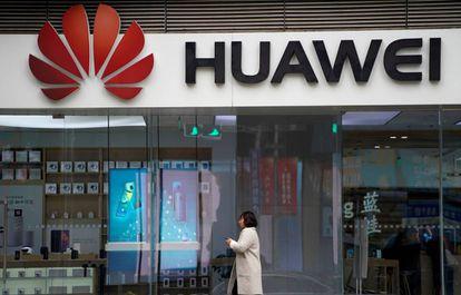Una mujer pasa caminando por delante de un logo de Huawei el pasado diciembre en un centro comercial de Shangái (China).