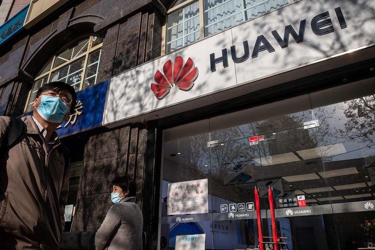 En esta foto de archivo tomada el 22 de abril, la gente pasa frente a una tienda de Huawei en Beijing.