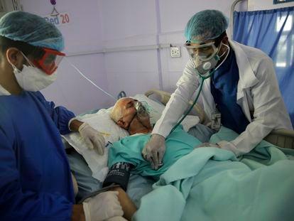 Dos sanitarios tratan a un enfermo de covid en Yemen.