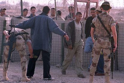 Soldados españoles cachean a civiles iraquíes en la base española de Diwaniya, en 2003.