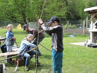 Niños suizos cortando ramas en un parque de aventura.