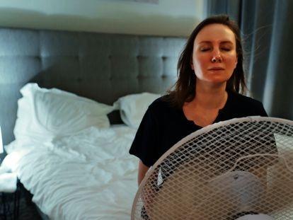 Una mujer intenta refrescarse frente a un ventilador.